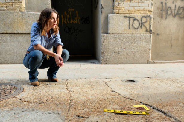 Emma Lahana as Detective O'Reilly crouching at a crime scene