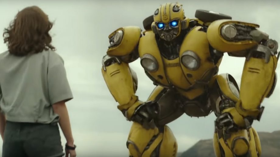 A young girl stands looking at a big yellow robot called Bumblebee