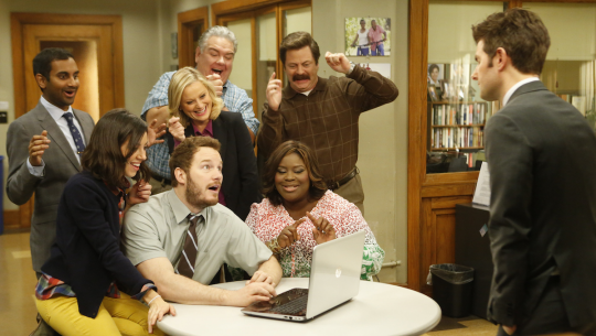 The cast of Parks and Rec looks at a laptop except for Ben who looks at the group