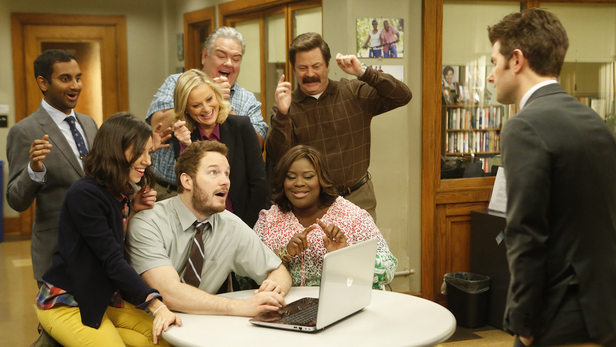The cast of Parks and Rec looks at a laptop, while Ben who looks at the group