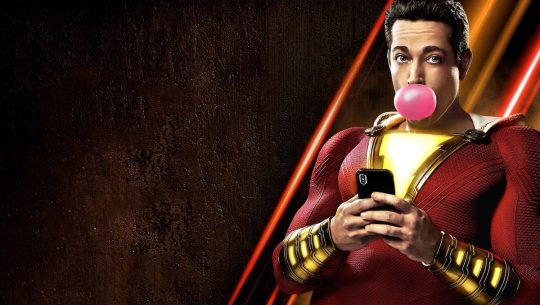 Shazam blowing a bubble and looking at a phone
