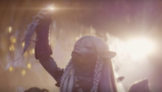 Brea in Dark Crystal: Age of Resistance holding something up with the sun behind her