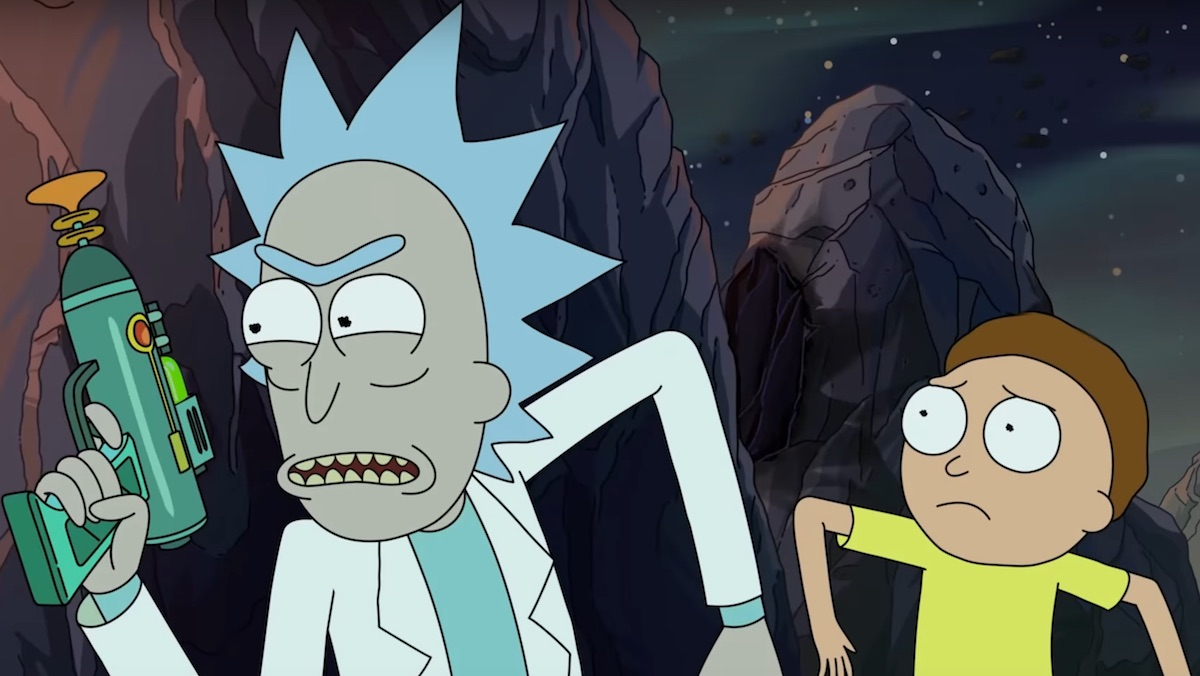 Rick holds a gun as him and Morty hide behind a rock