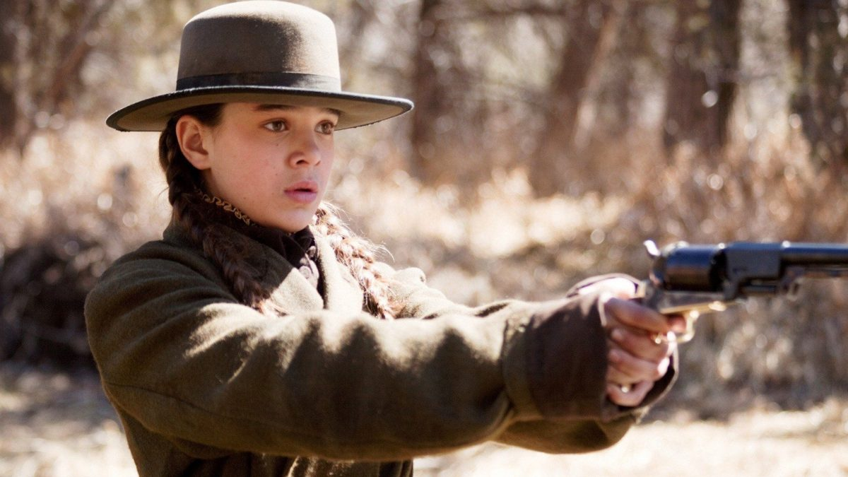 A young Hailee Steinfeld wields a gun in the Old West.