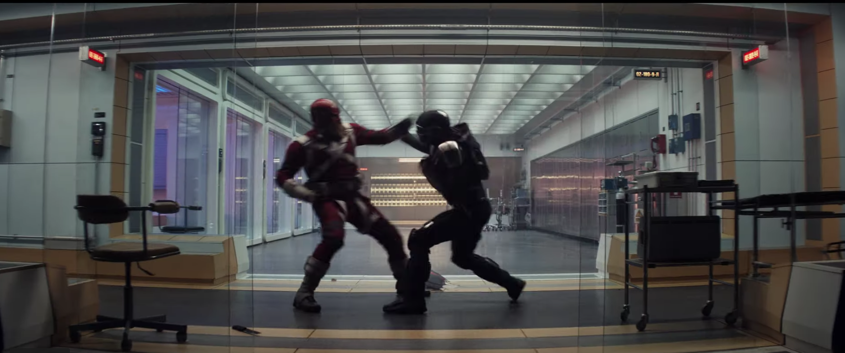 Two costumed agents fight in an office setting.