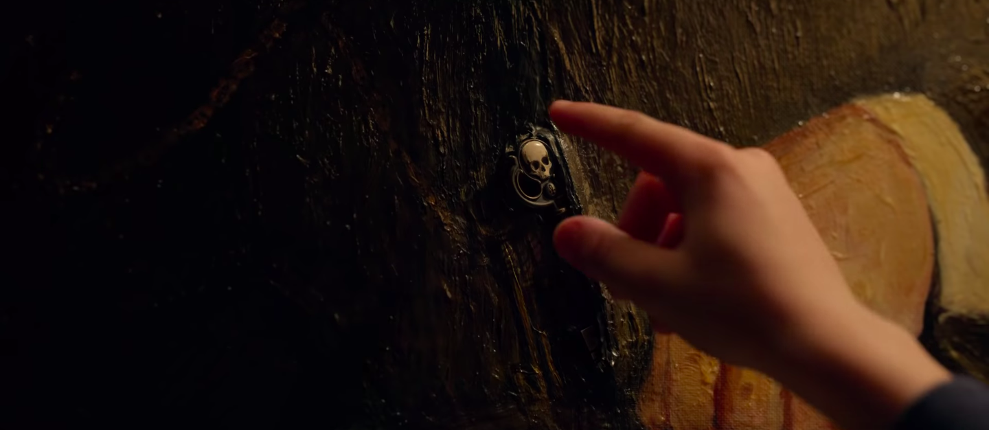 A scary looking skull key is being reached for by a child's hand
