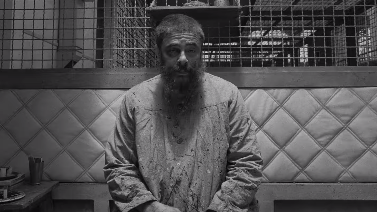A prison inmate (Benicio del Toro) sits in a padded cell.