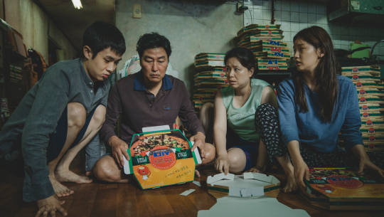 The Kim family folds pizza boxes for cash in their underground apartment in Parasite.