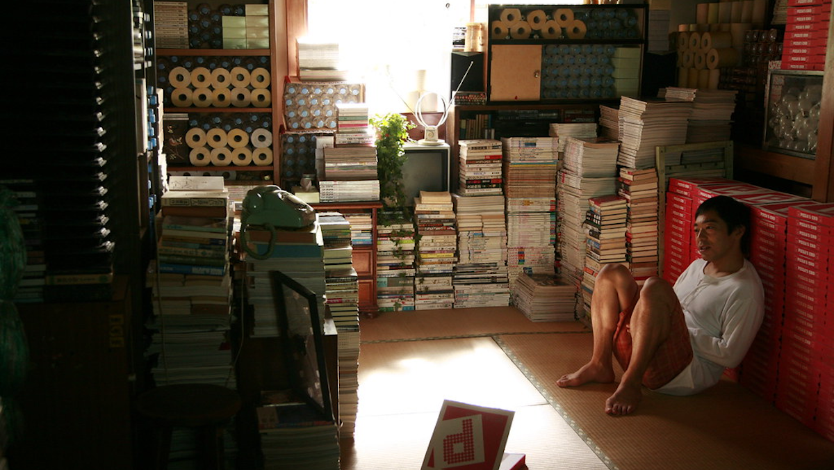 A man sits in a room filled with pizza boxes.