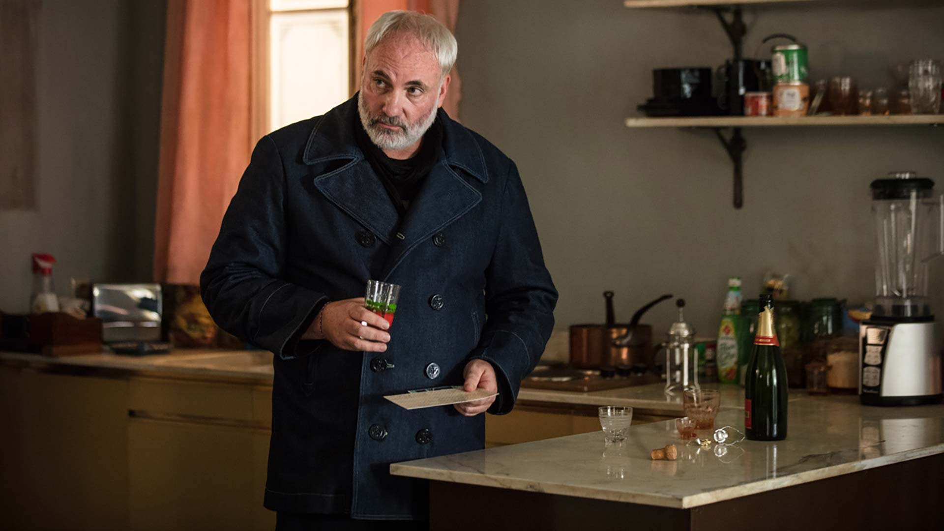 Konstantin Vasiliev holds a drink in Killing Eve