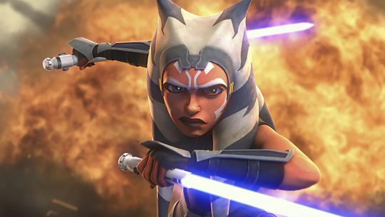 Ahsoka wields lightsabers in front of an explosion