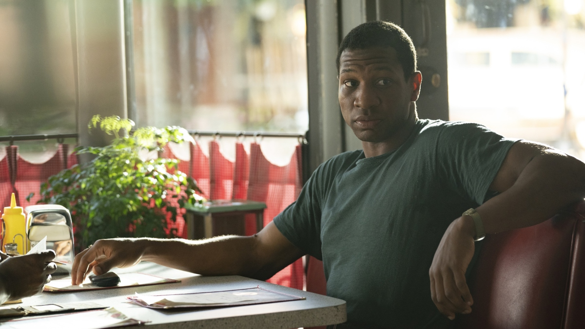 A Black man in a green shirt sits in a red diner booth