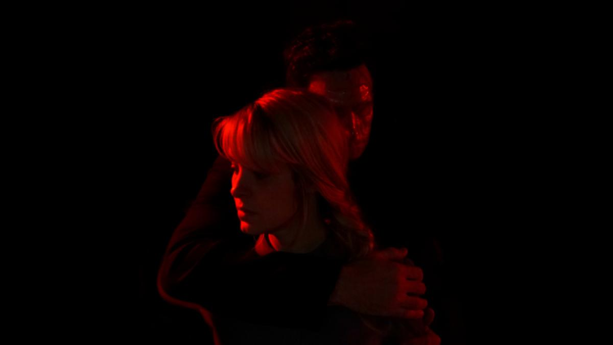 Brea Grant's May is embraced by a stalker stranger and drenched in red light in a still from the Shudder horror film Lucky.
