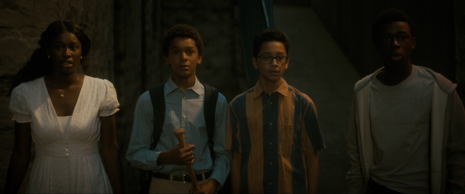 Three boys and a girl stand side by side in a dark room