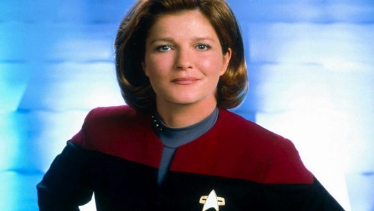 Captain Janeway smiles to the camera