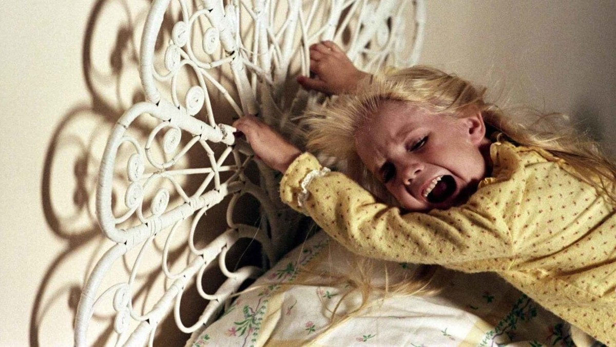A young girl holds onto the headboard of her bed in Poltergeist.