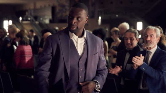 Lupin Assante Diop man in suit walks through a crowd