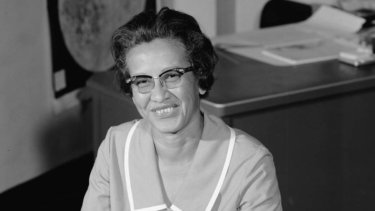 A black and white photo of Katherine Johnson sitting at her desk at NASA.