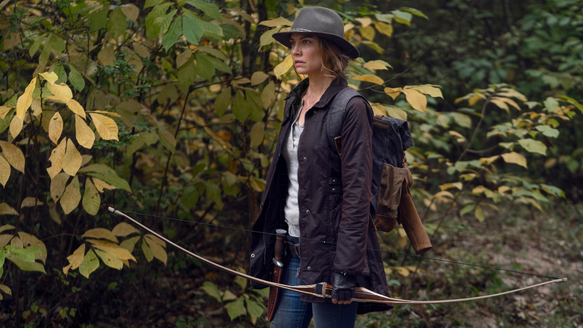 A photo of a woman wearing a brown hat and standing near trees while holding a bow and arrow on The Walking Dead