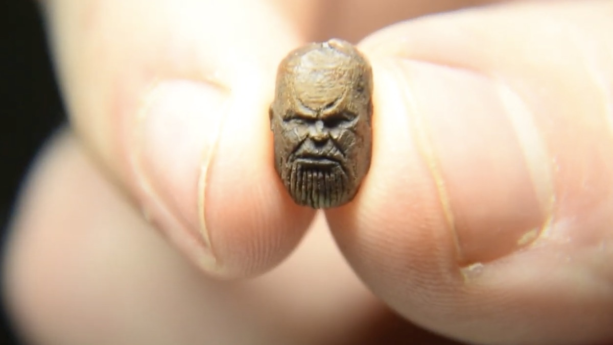 Two fingers hold a tiny sculpture of Thanos's head made out of a coffee bean