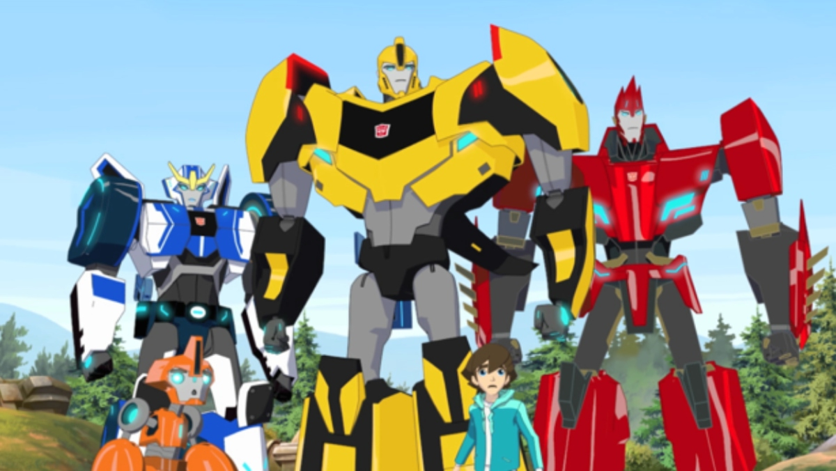 Several animated Transformers robots stand together with a human boy in various colors like red, blue, and yellow