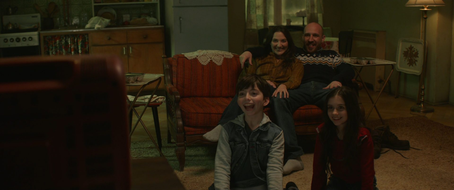 Young Wanda watches TV with her family in a WandaVision flashback.
