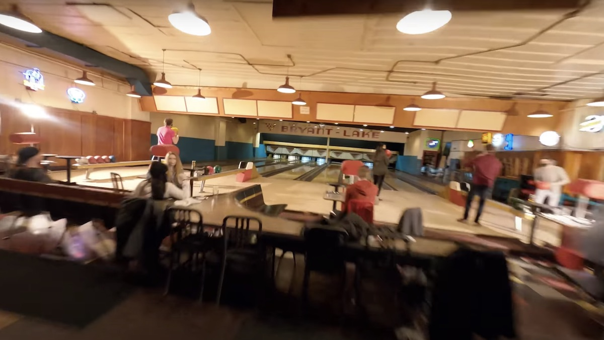 A bowling alley as seen from a drone behind the players who are playing/facing the pins