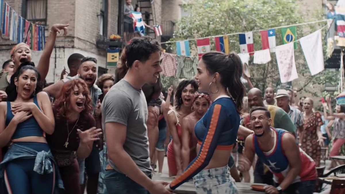 A man and a woman hold hands outside while a large group surrounds them and cheers them on in Warner Bros. In the Heights