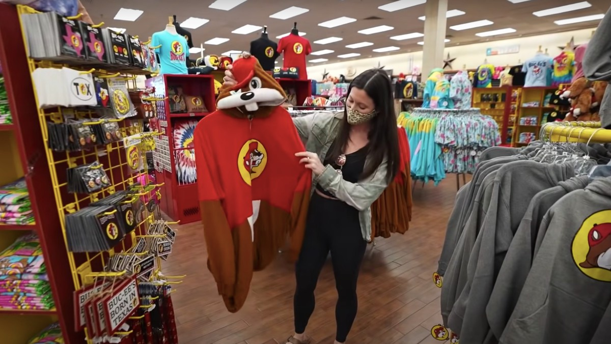 YouTuber Kara from the travel vlog channel Kara and Nate holds up a Bucky the beaver costume at a Buc-ee's in Texas, the largest gas station in the world.