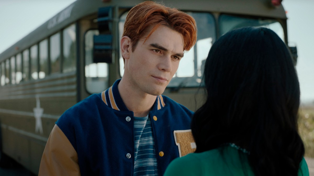 Archie Andrews wears a letterman jacket and stands before a bus talking to Veronica in a scene from Riverdale.