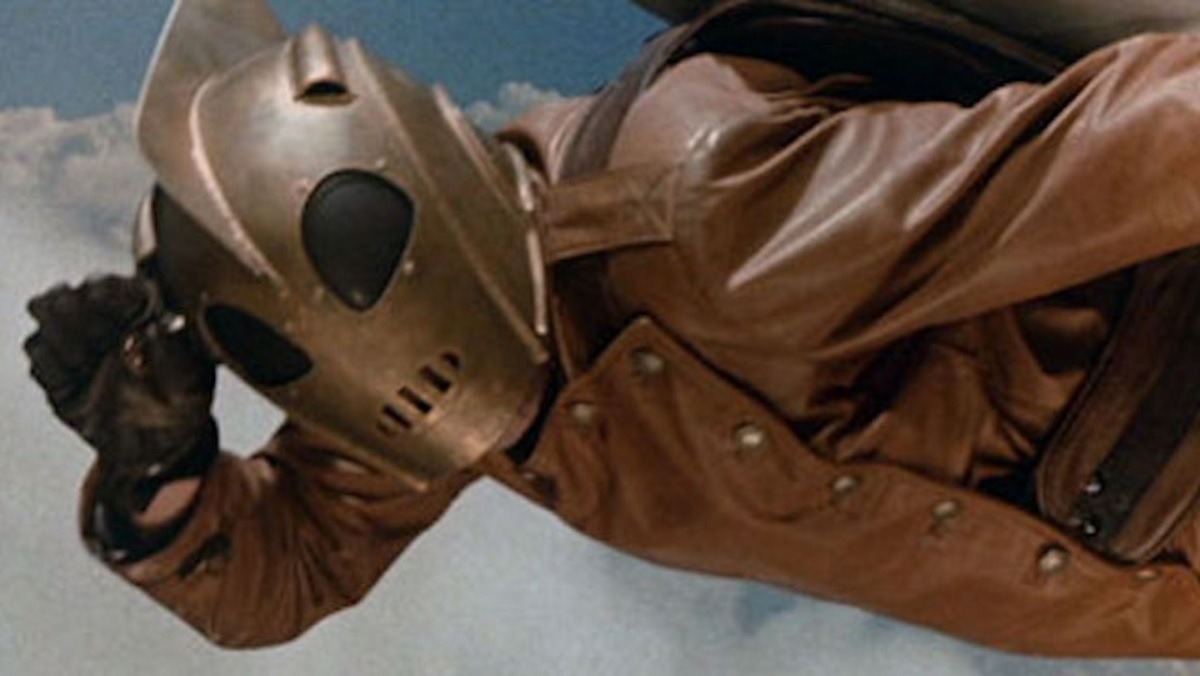 The Rocketeer salutes while flying in the sky.
