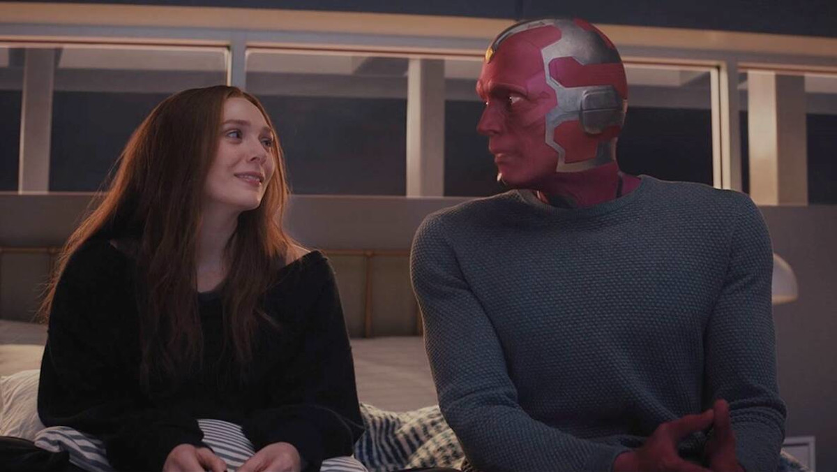 Wanda looking at Vision as they sit on her bed in WandaVision