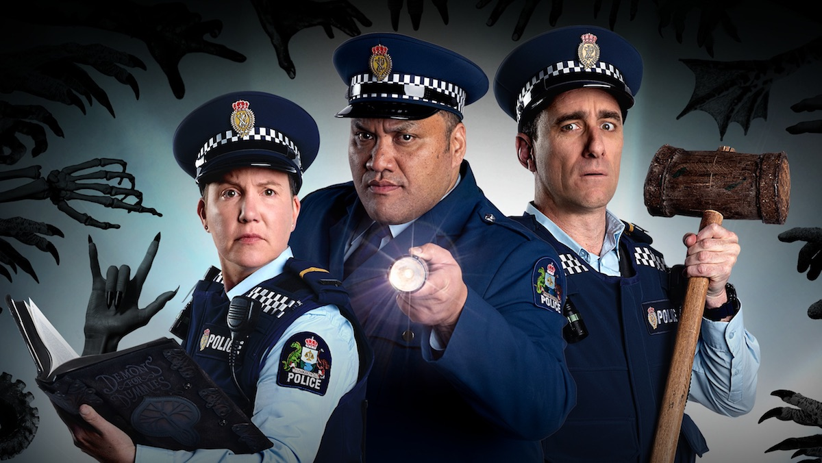 Three police officers look at the camera while black demon hands reach out for them in a publicity shot for Wellington Paranormal