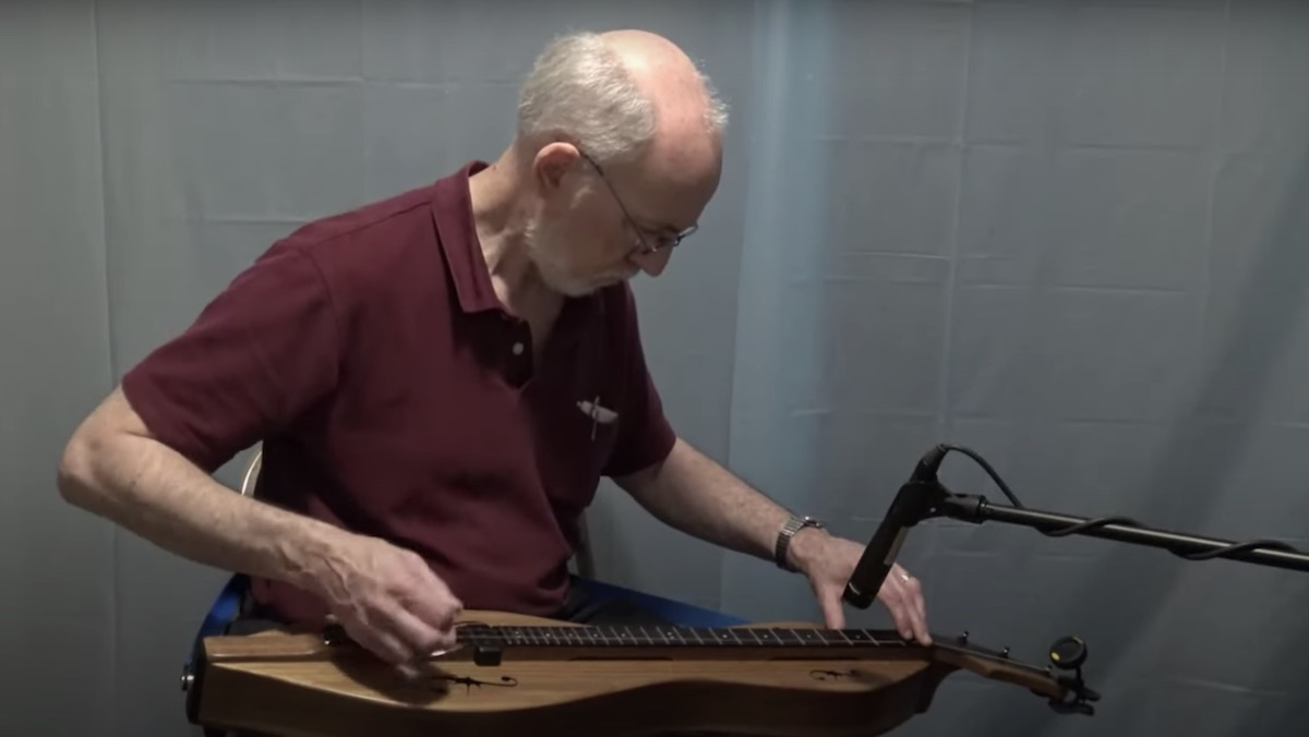 An older man plays a dulcimer against a gray background
