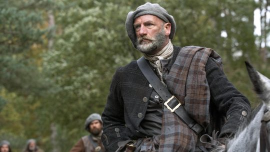 A man in traditional Scottish clothes sits on a horse in the woods