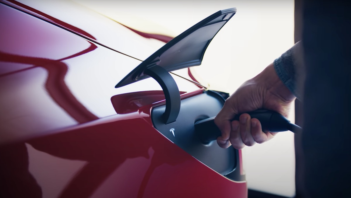 The charging port of a Tesla with a hand holding the charge cable in it