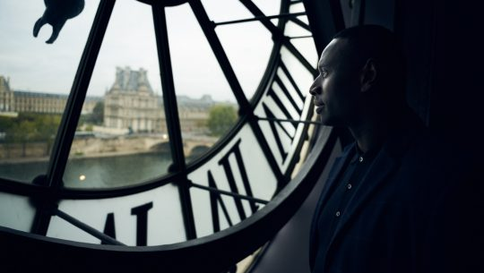 A photo of a man standing inside London's Big Ben and looking out at the city in Netflix show Lupin