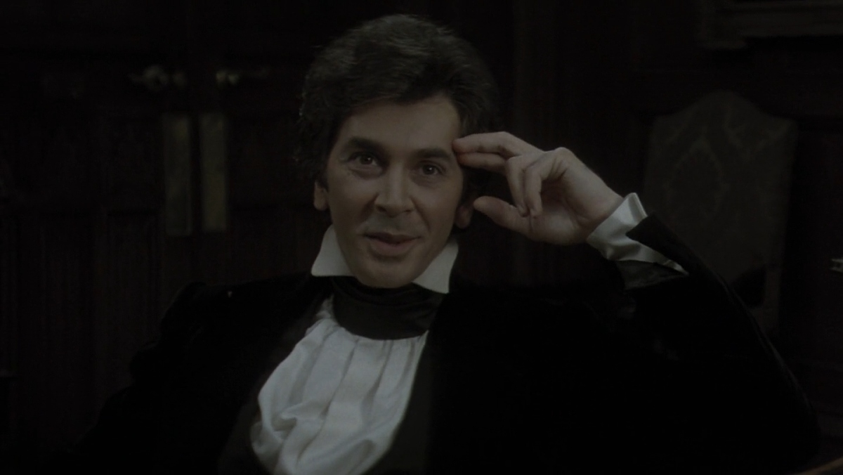 Frank Langella as Dracula sits in a corner with books behind him and wearing a black velvet coat and white shirt