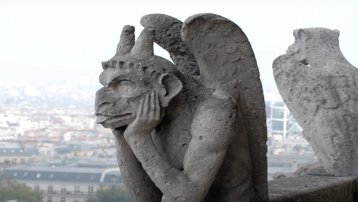 A winged stone gargoyle that rests its face on its hands
