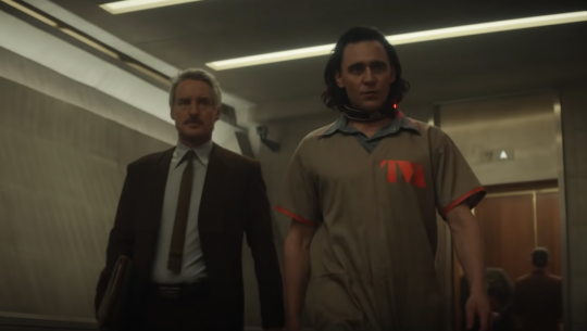 Mobius (in a suit) and Loki (in a prison uniform) walk down a hallway together.