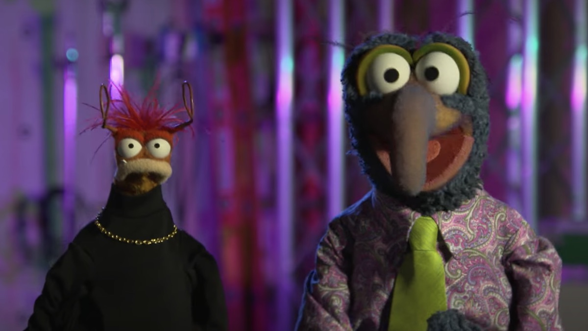 Pepe the King Prawn in a black turtleneck and chain standinmg nexct to Gonzo in a flashy shirt with green neon tie