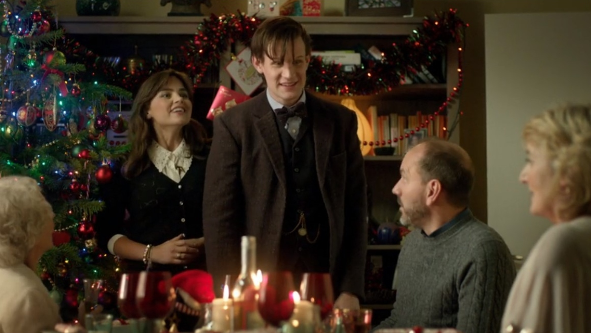 clara and the eleventh doctor stand in front of a christmas tree and fireplace with her parents sitting at a table in front of them