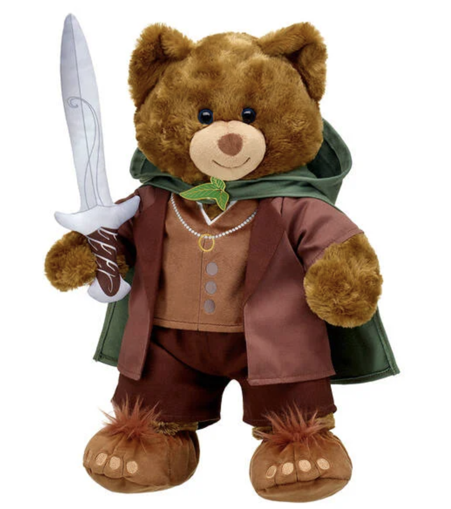 A teddy bear dressed like The Lord of the Rings' Frodo, with a cloak, jacket, and sword in hand