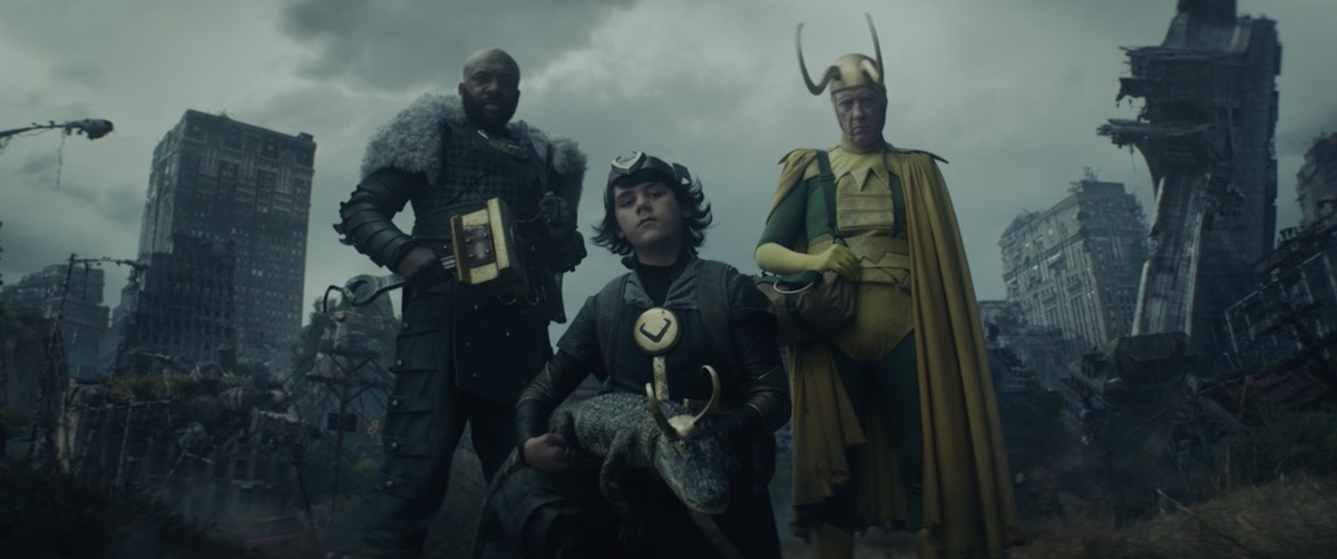Loki Variants huddle together looking down as a destroyed New York City with a ruined Stark Tower looms behind them