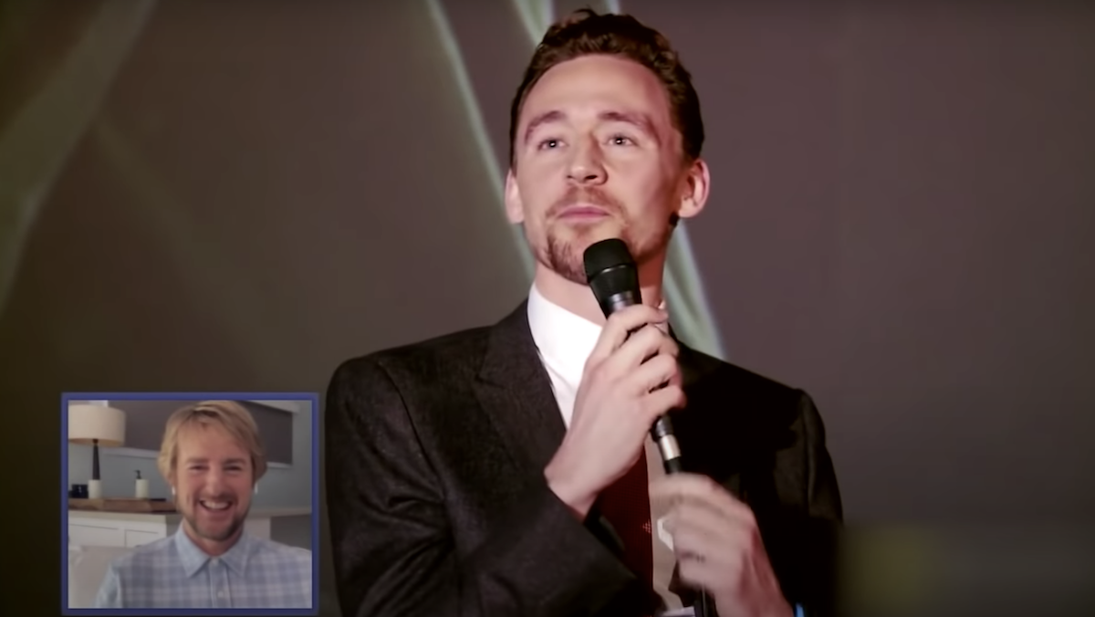 Tom Hiddleston talks into a microphone, while Owen Wilson, in a small box, watches