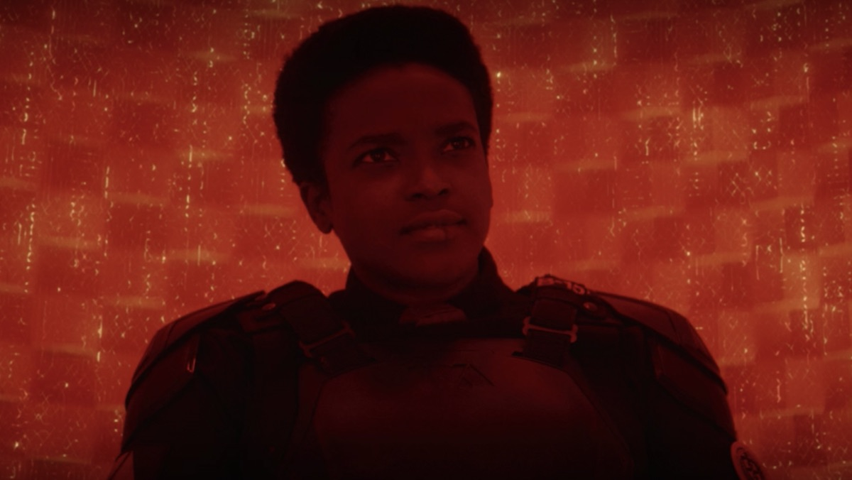 A woman in a black military suit sits in a red room looking stern