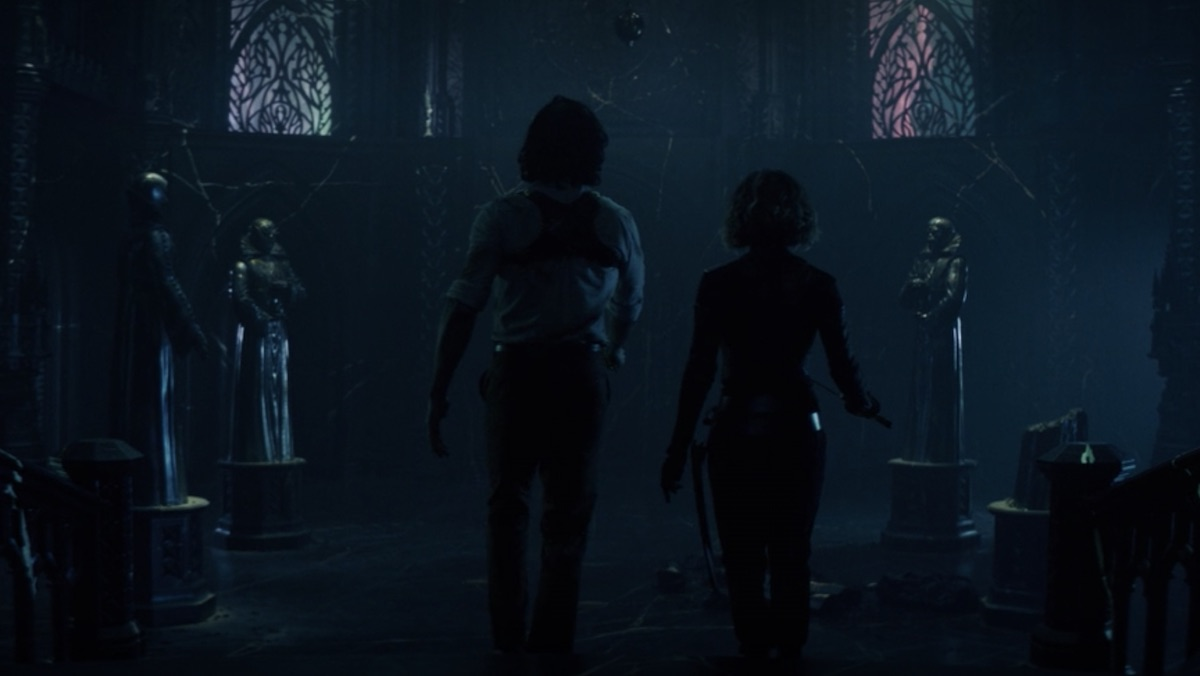 Loki and Sylvie walk into the Citadel's atrium which has three standing statues and one broken one on the floor