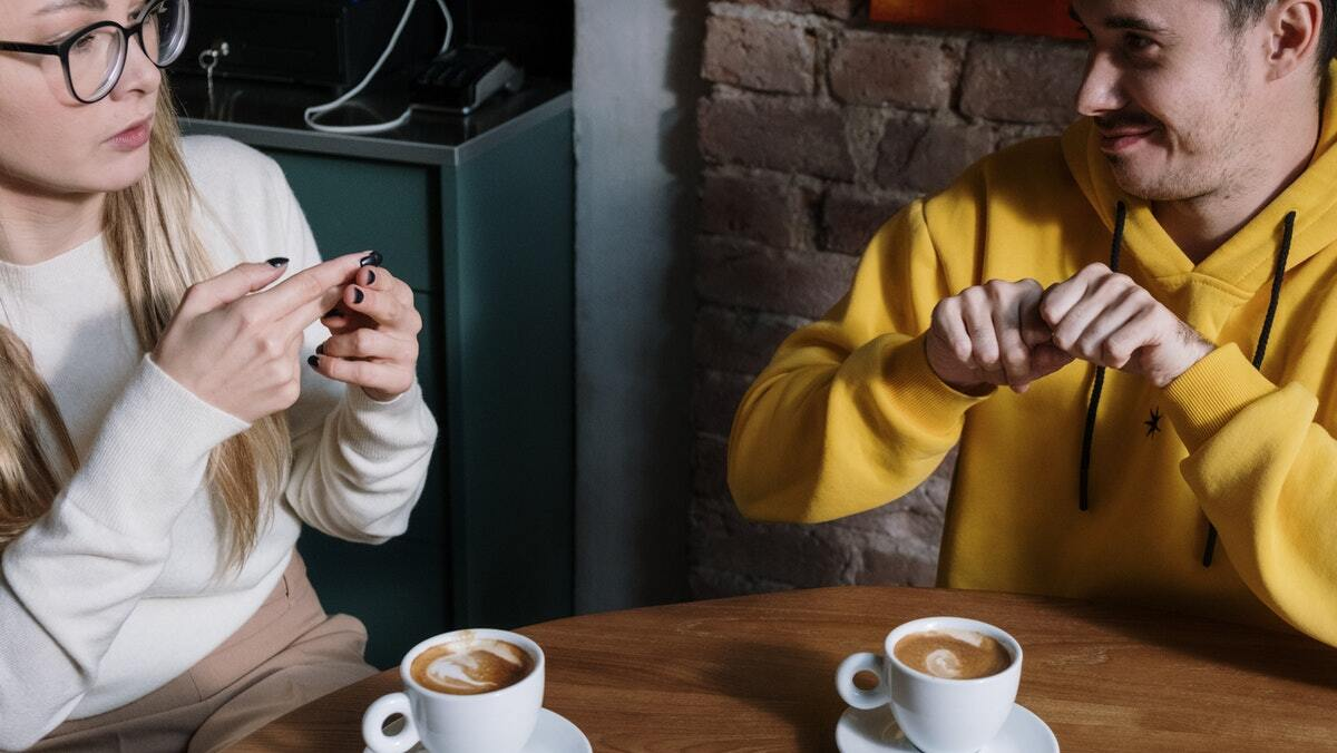 woman in glasses and white sweater sitting at a table with a man in an orange sweater signing ASL over coffee