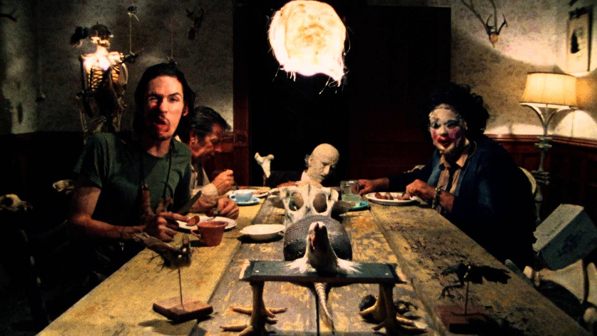 A family of cannibals, including a corpse-like old grandpa, stare at the camera and laugh in Texas Chainsaw Massacre.