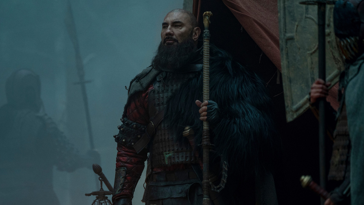 Dave Bautista stands outside a tent holding a staff